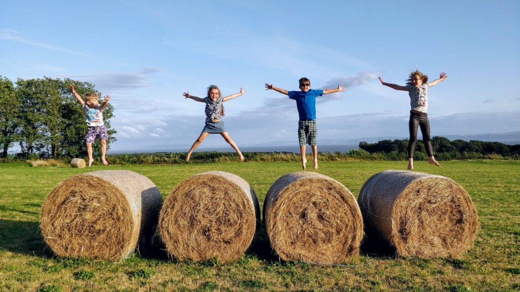 kids jumping on hay bales